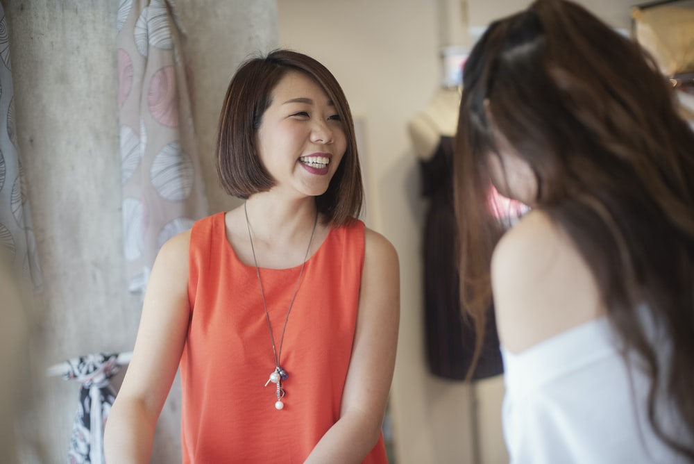 woman in orange tank top smiles beside woman