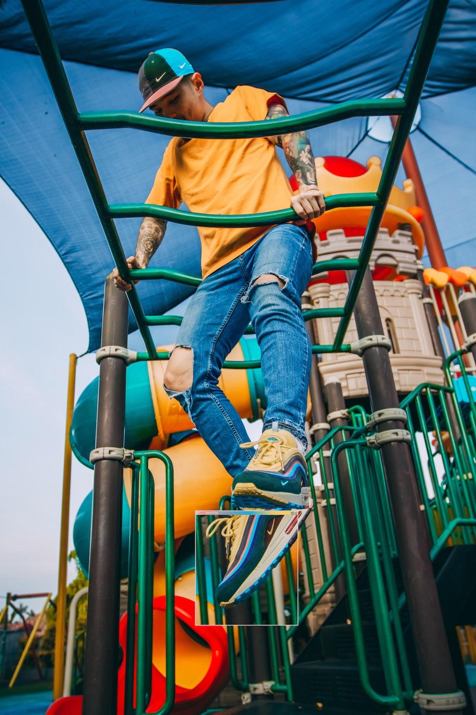 man hanging on green monkey bar