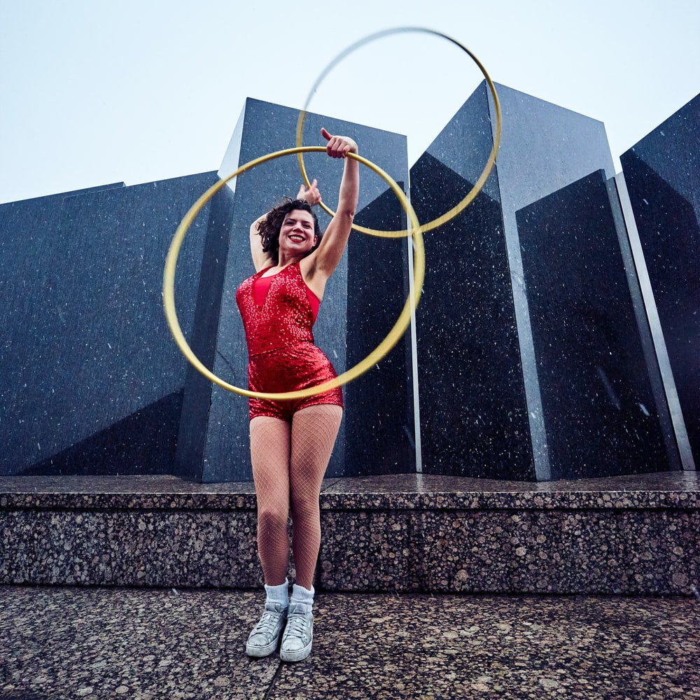 woman in red suit holding hula hoops