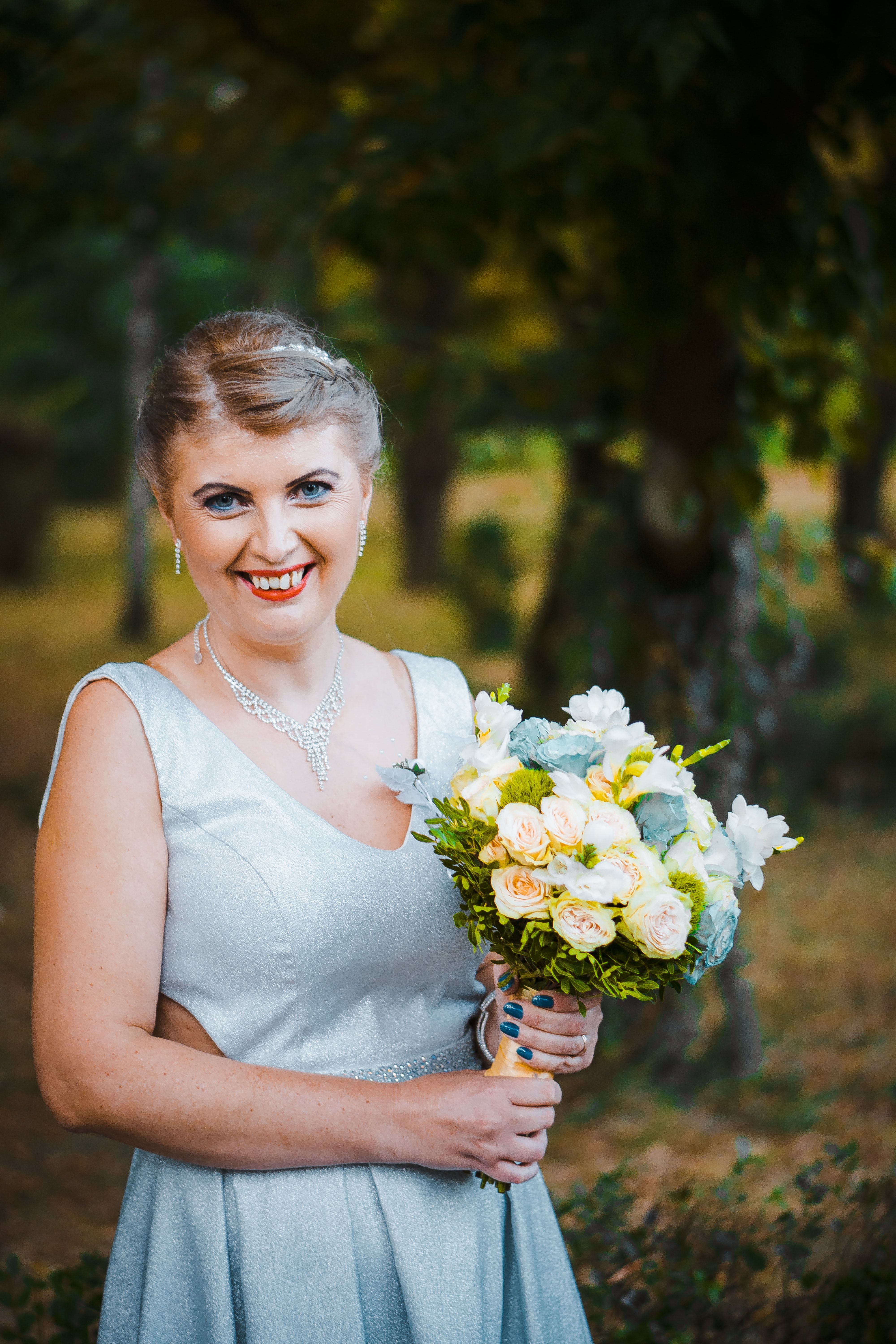 shallow focus photo of woman in sleeveless dress holding flowers