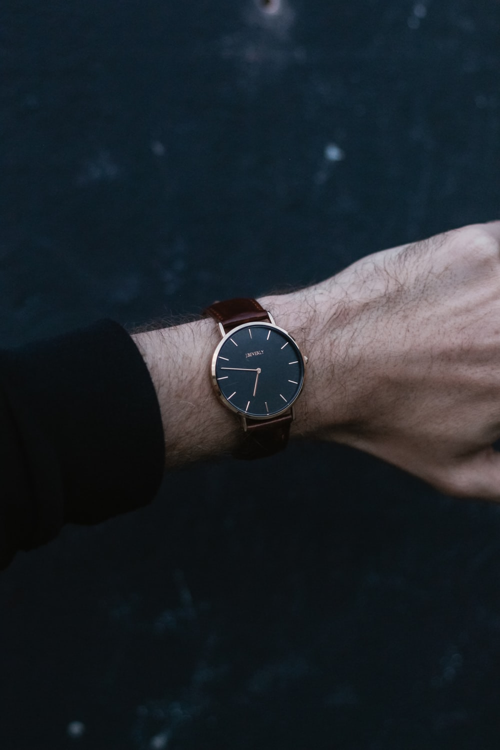 person wears analog watch reading 06:47