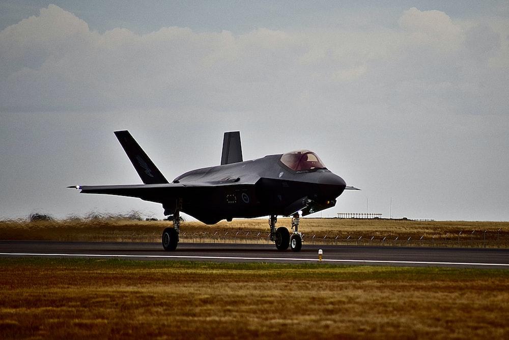 black fighter plane on road