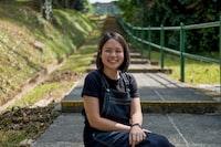 smiling woman sitting on paveway