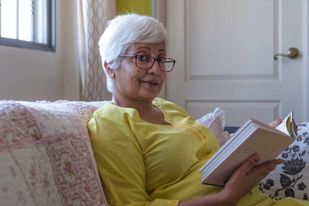 woman reading book while sitting on sofa