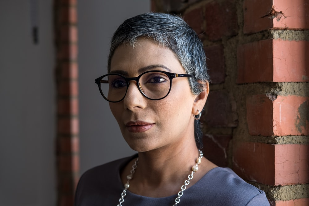 woman wearing black framed eyeglasses learning on red brick wall