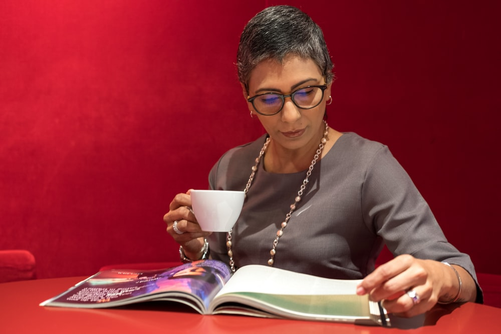 woman in grey shirt reading magazine while having coffee
