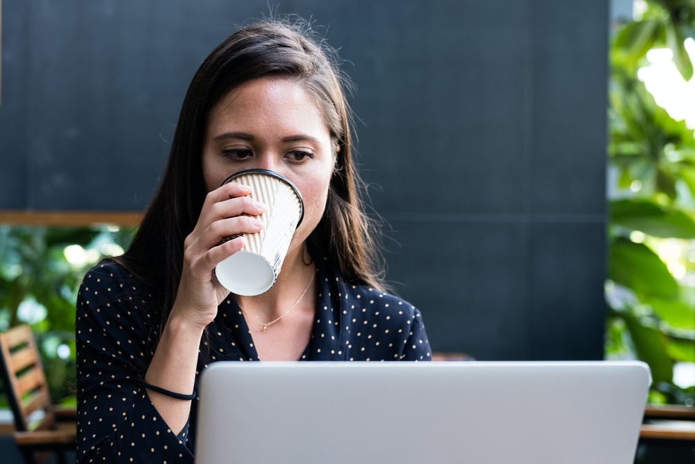 woman facing laptop while holding disposable cup