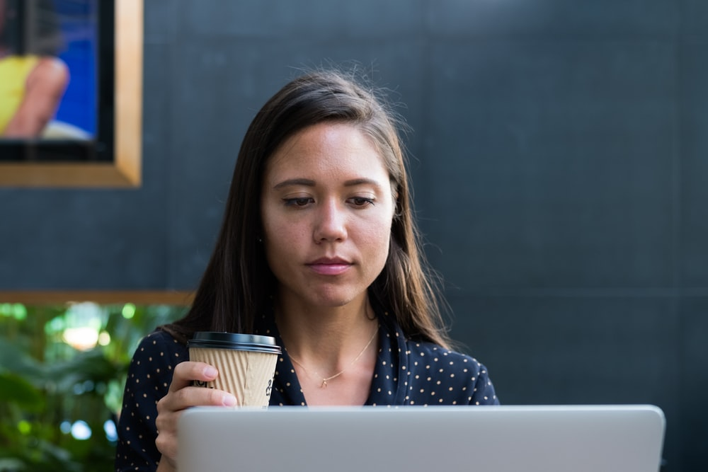 woman looking at white laptop