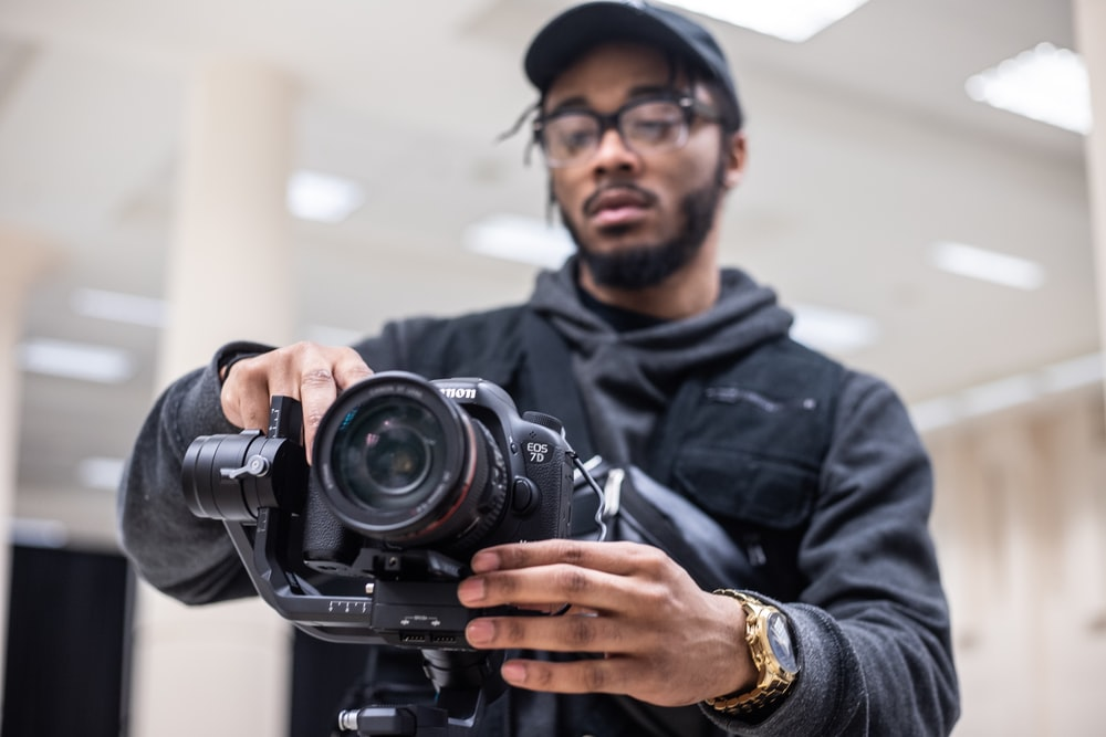 man using black Canon DSLR camera