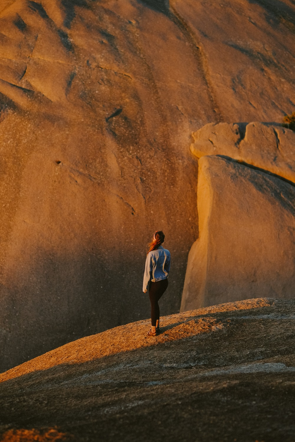 woman in white shirt standing on rock by cliff during golden hour