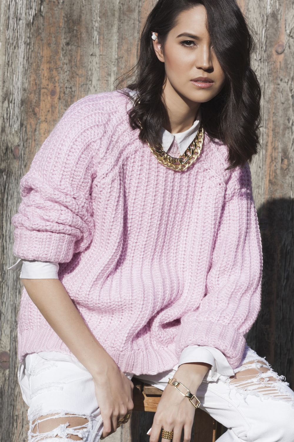 women in pink knitted sweater sitting by woode wall