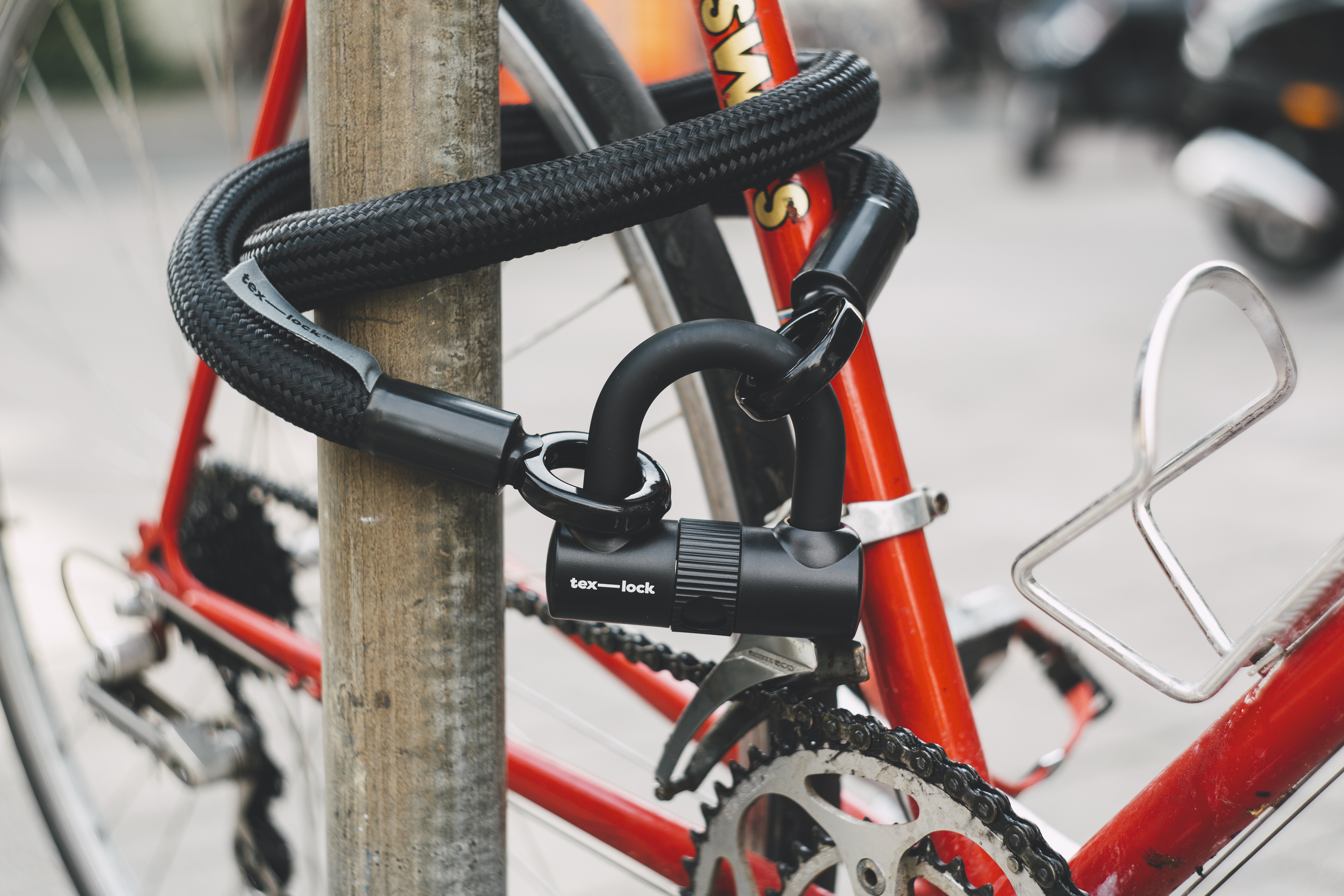 orange bicycle tired with cable lock
