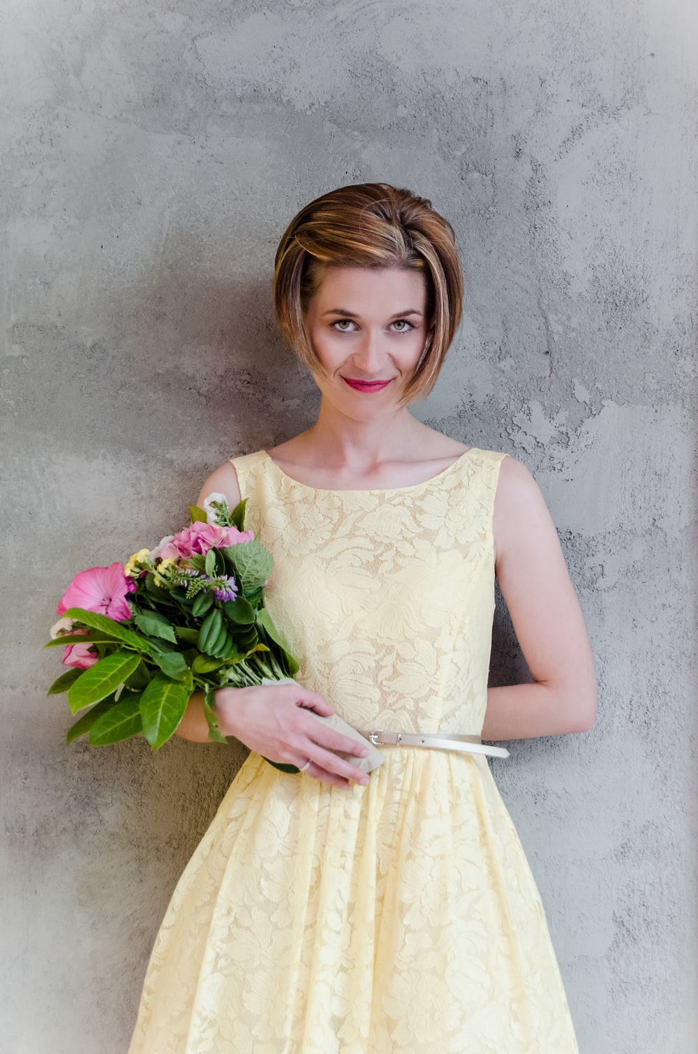 woman in yellow floral dress carries pink flower bouquet