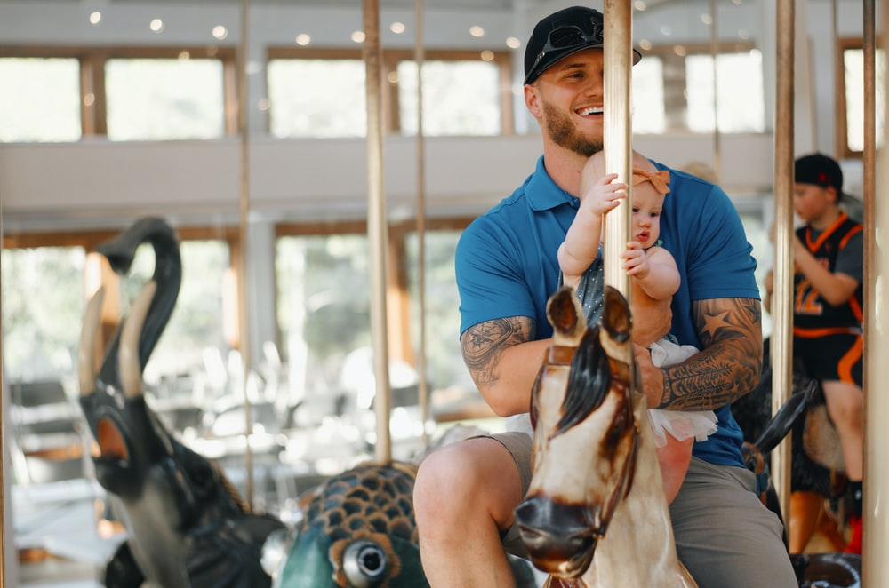 man riding horse carousel with baby