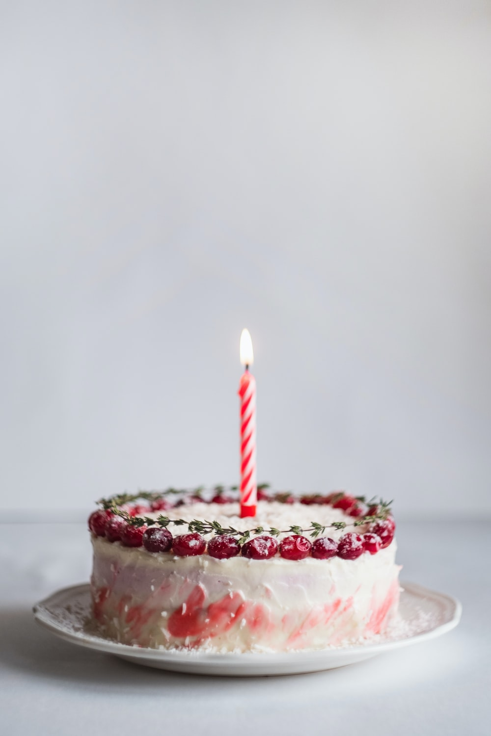 white and pink covered cake with lightened candle