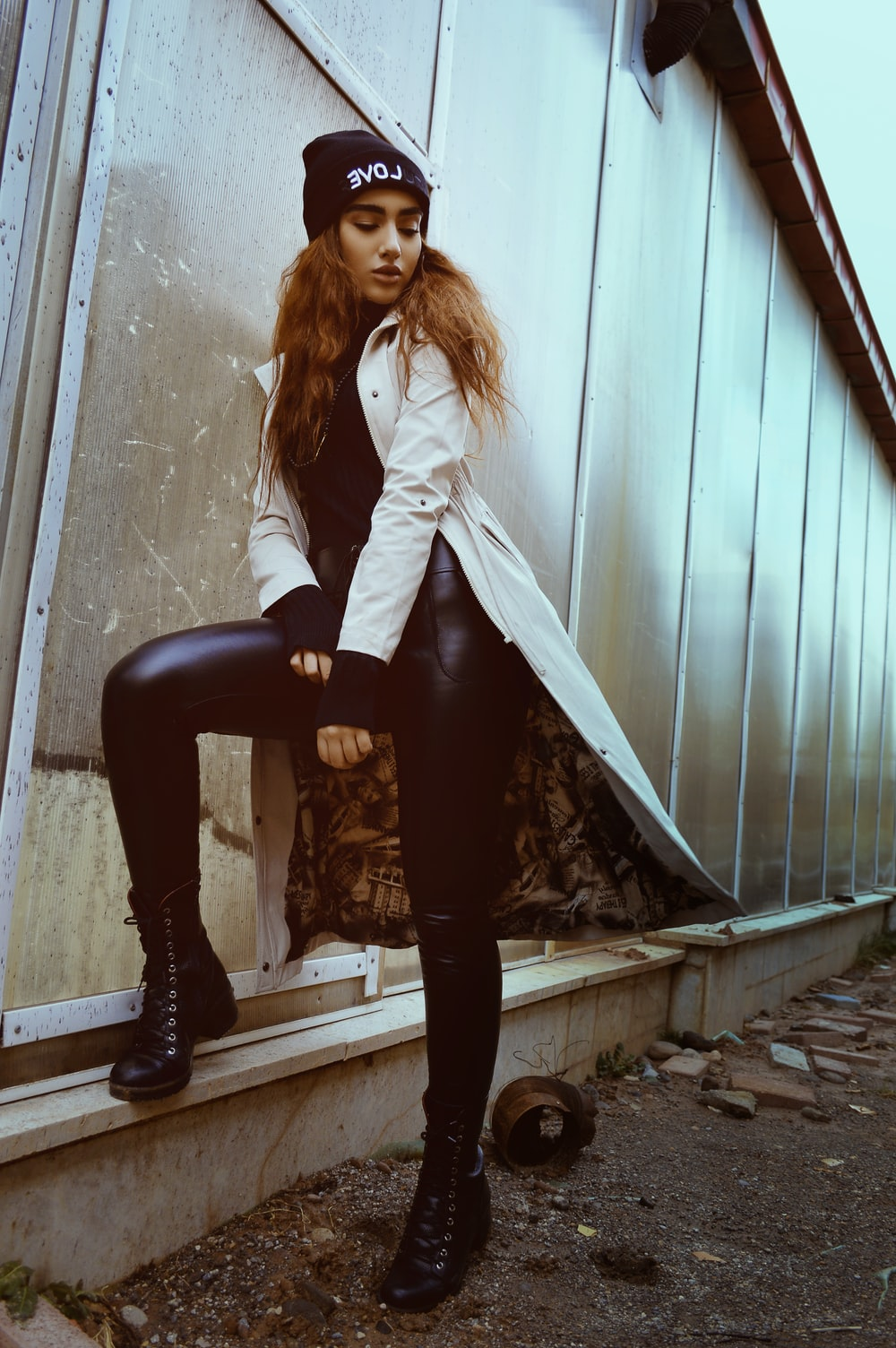 woman in white coat and black leggings standing beside wall