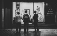 three people standing near store
