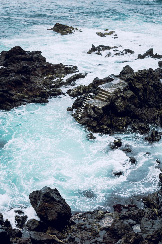 stairs on gray rock near ocean