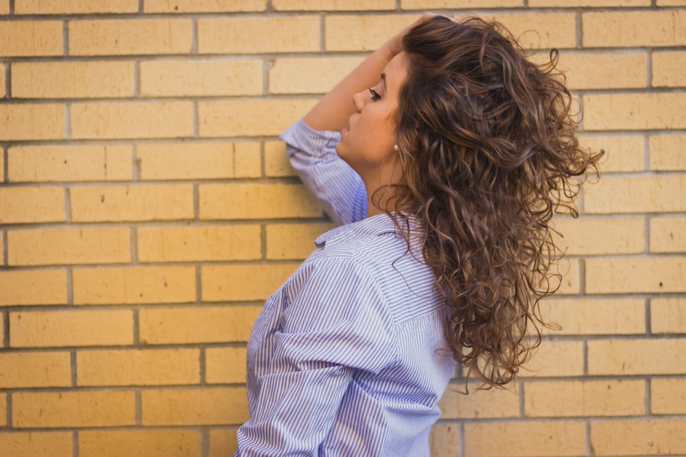 woman in gray dress shirt near brick wall