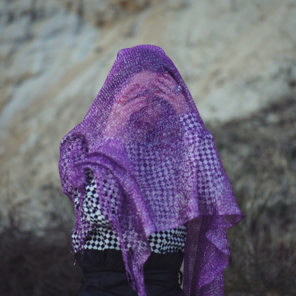 selective focus photography of woman wearing purple scarf
