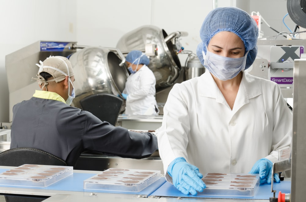 three people inside factory wearing masks and coats