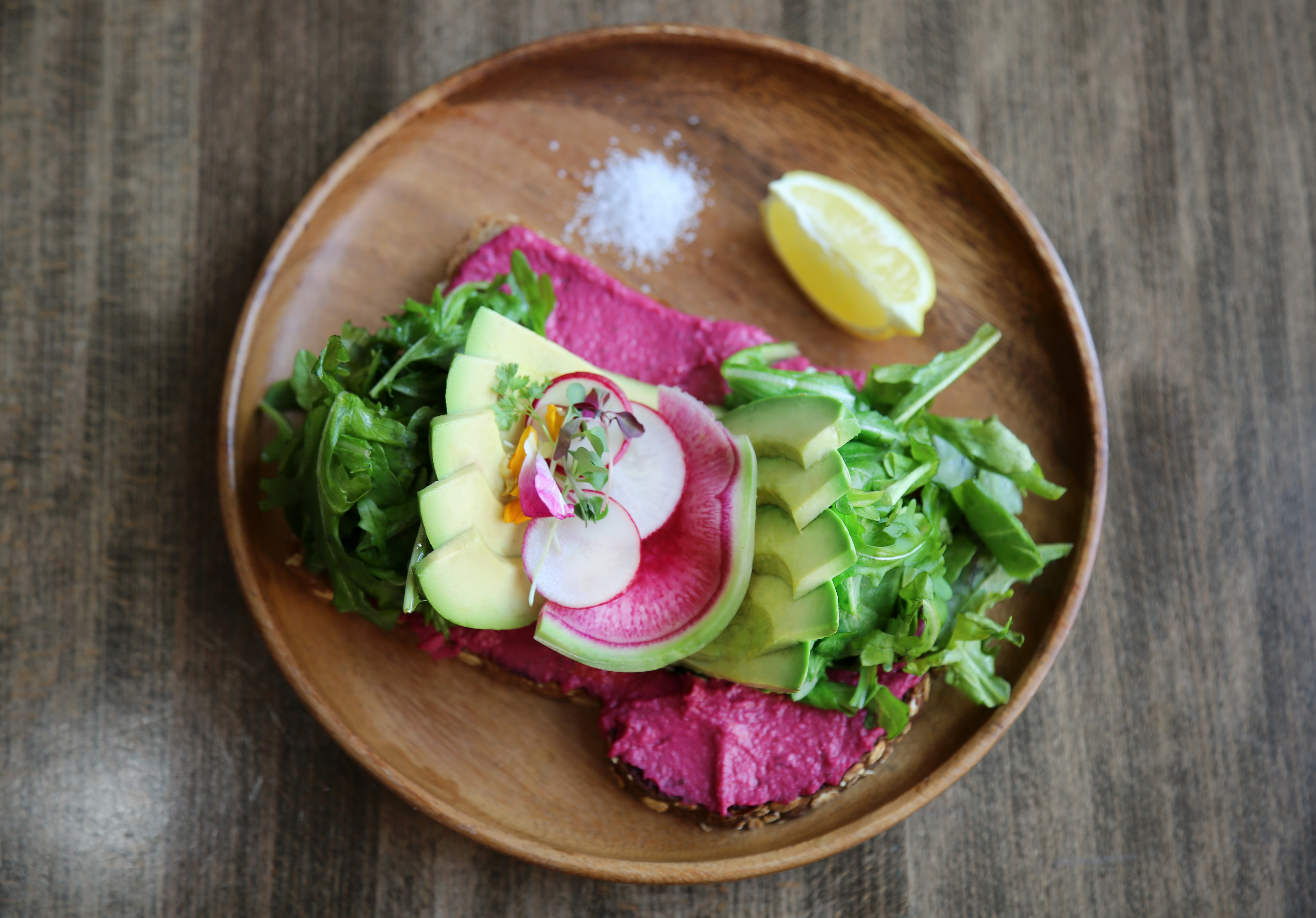 sliced cabbage, avocado and lemon on plate