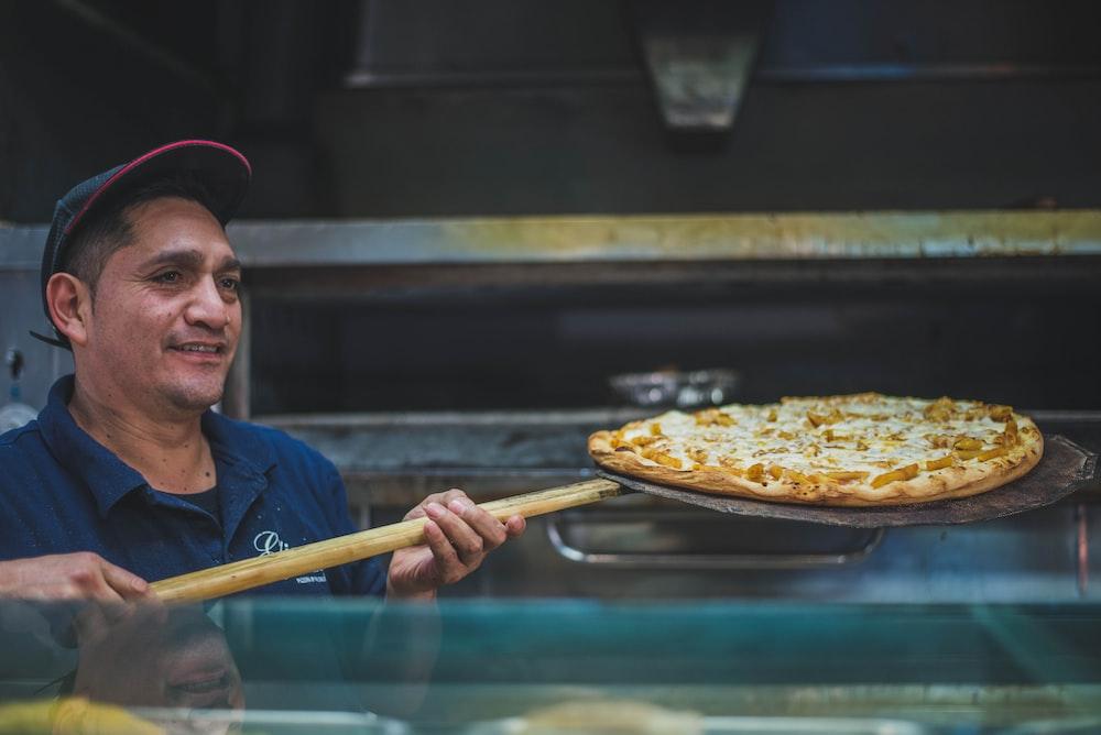 man holding pizza on holder