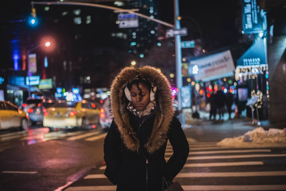 woman standing wearing parka coat at night-time
