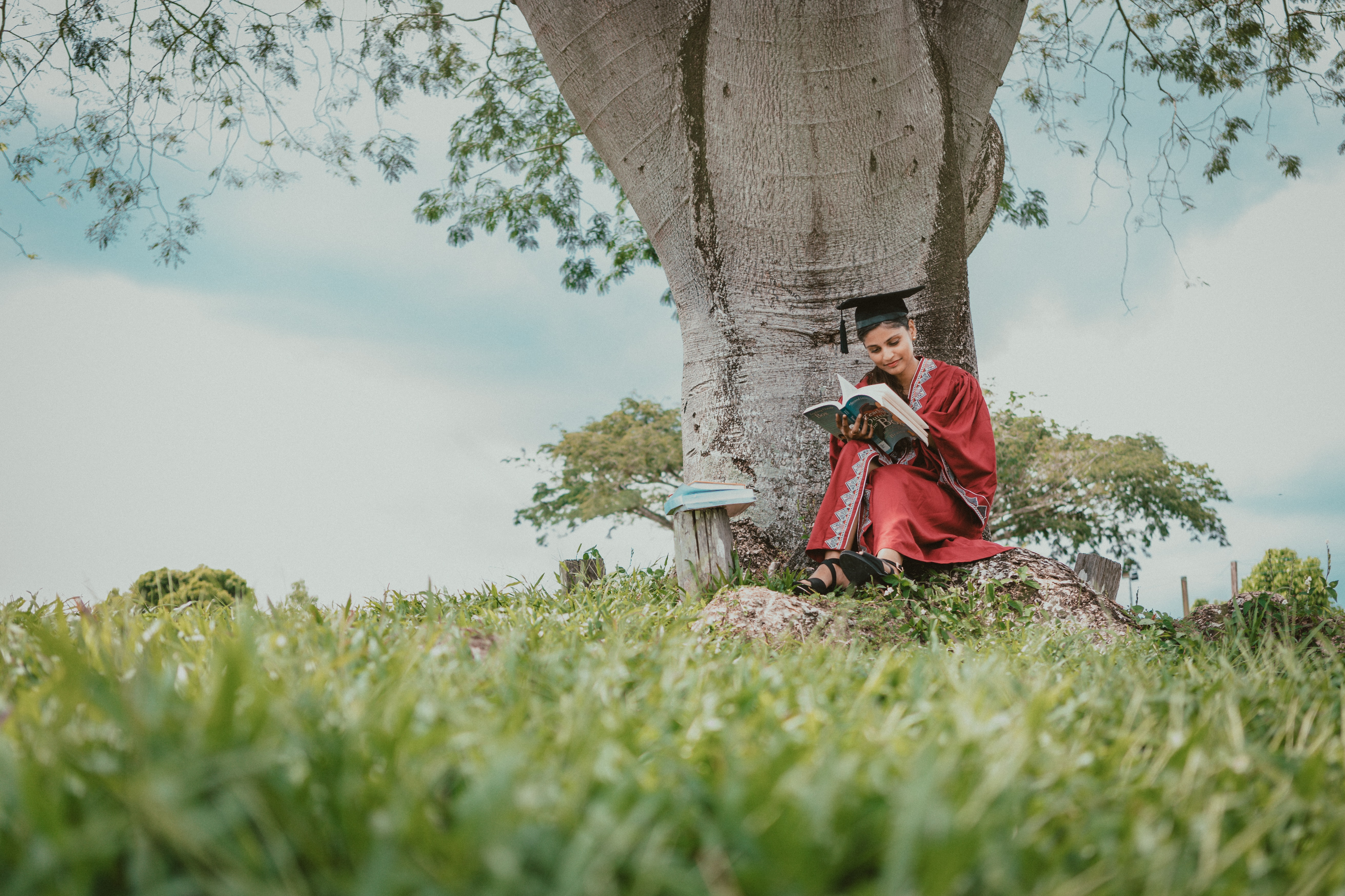 woman in red robe sitting under the tree and reading book