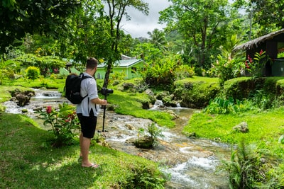 man in grey shirt and black shorts standing by the river bank near house during daytime vanuatu teams background