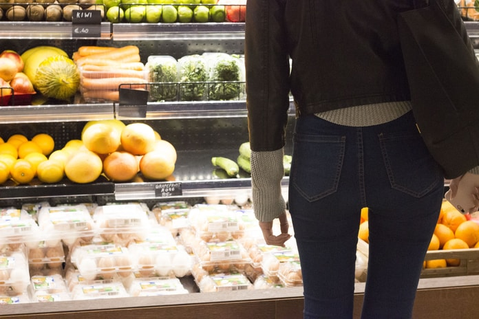 woman standing front of vegetables and fruits