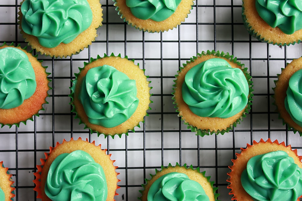 green cupcakes on black and white lined mat