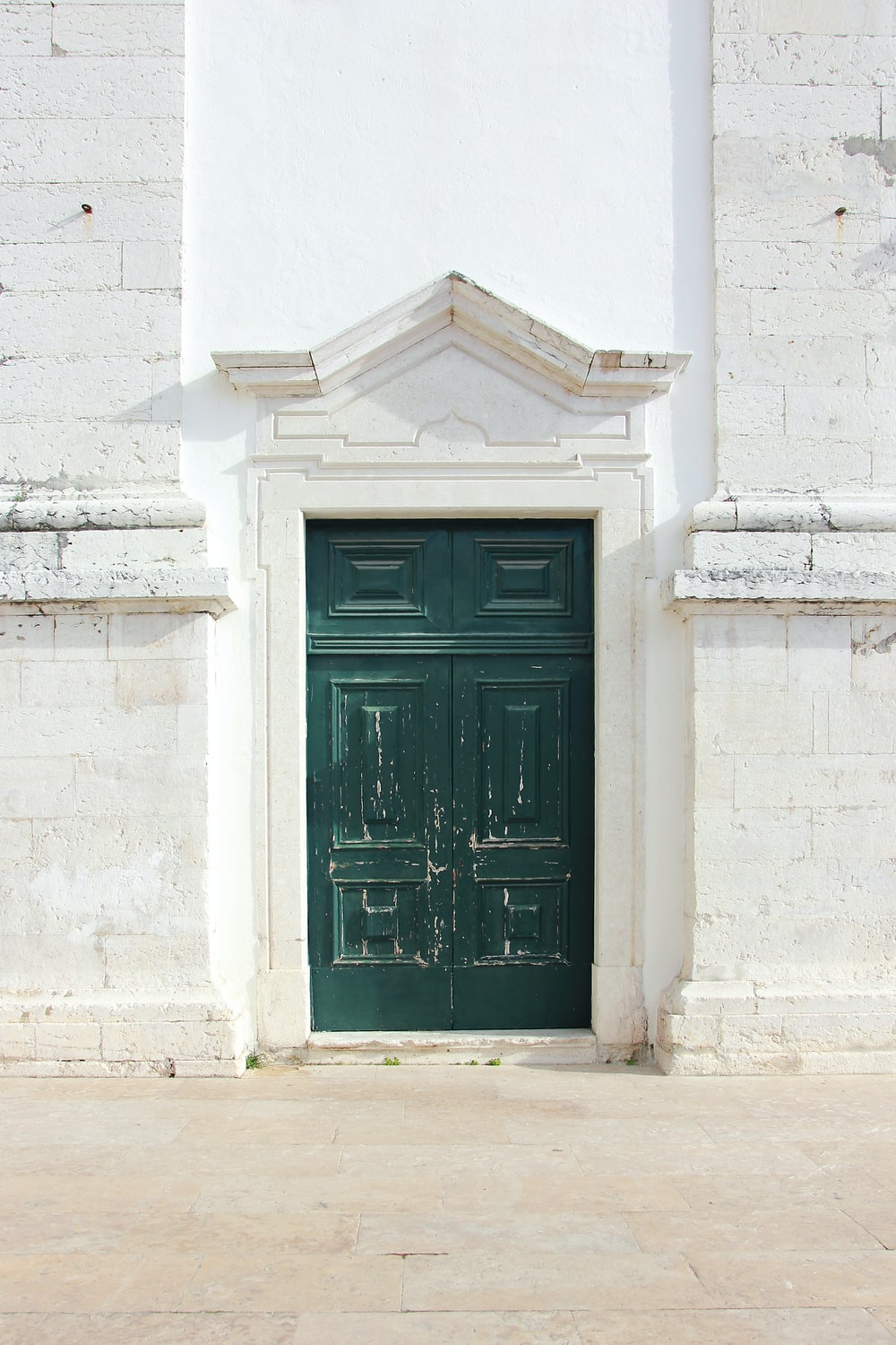 green wooden door with white wall