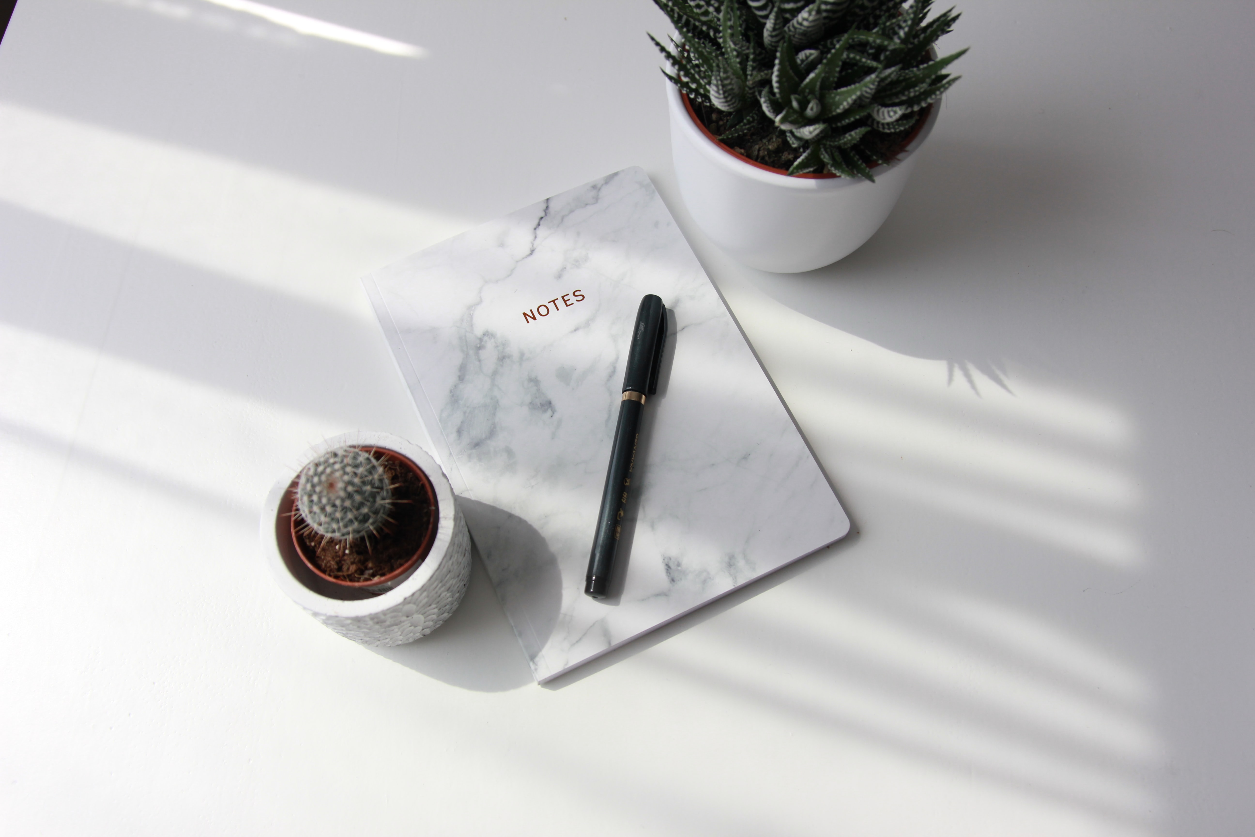 white book and black pen on table