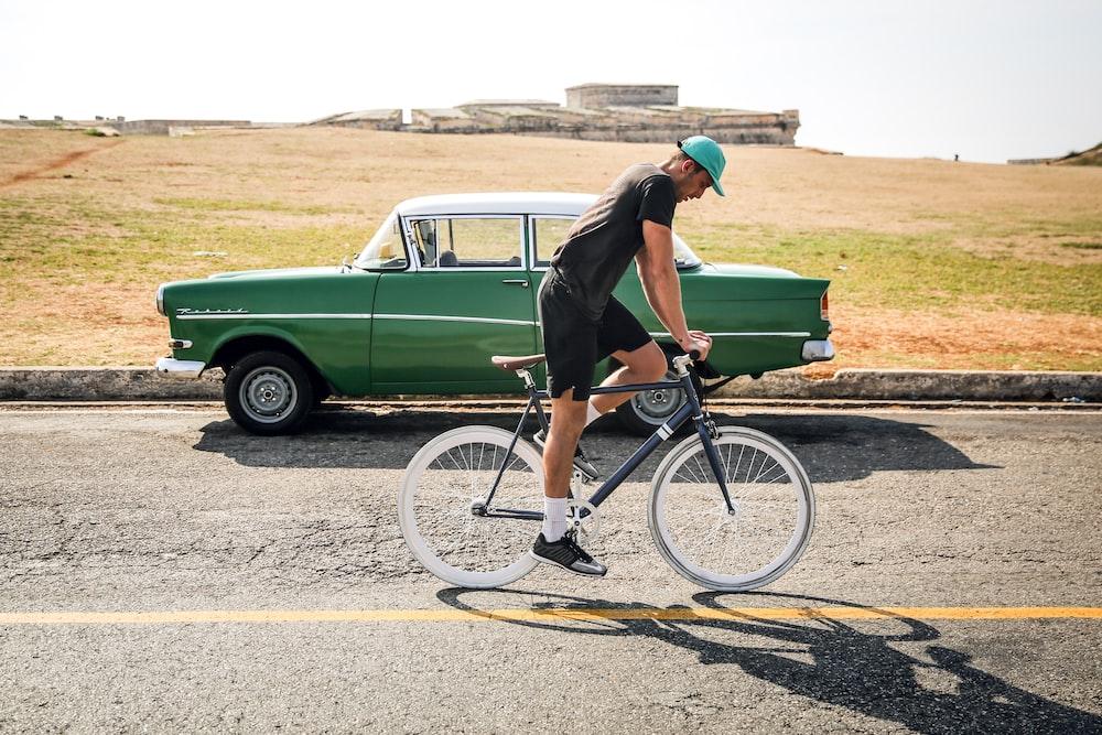 man riding on black road bike