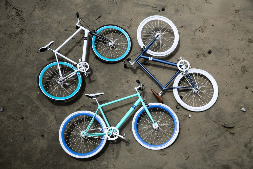 three road bikes on gray pavement