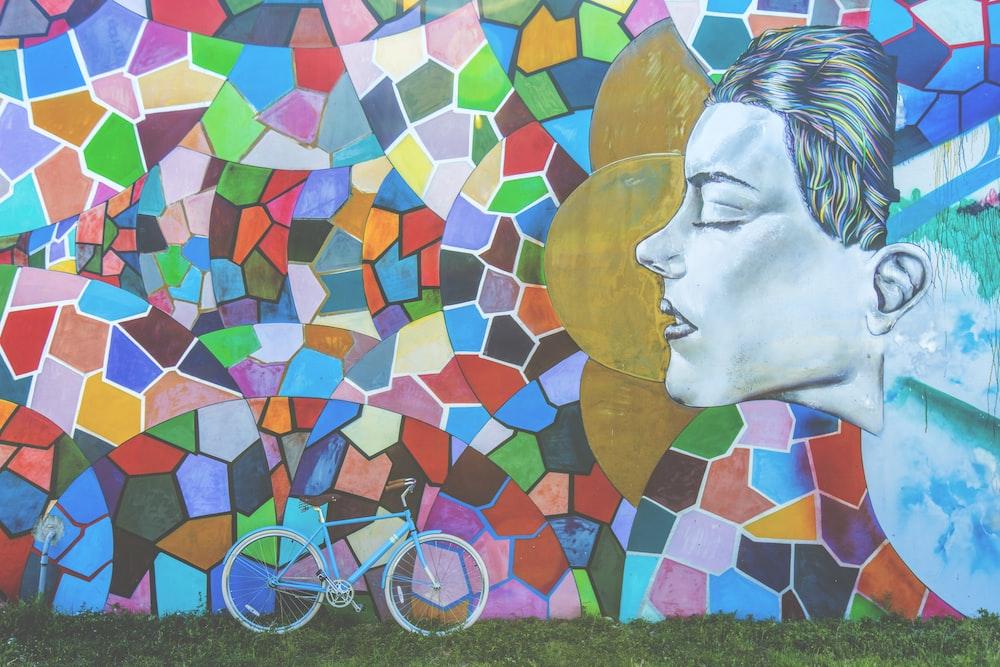 blue bike leaning beside mural wall