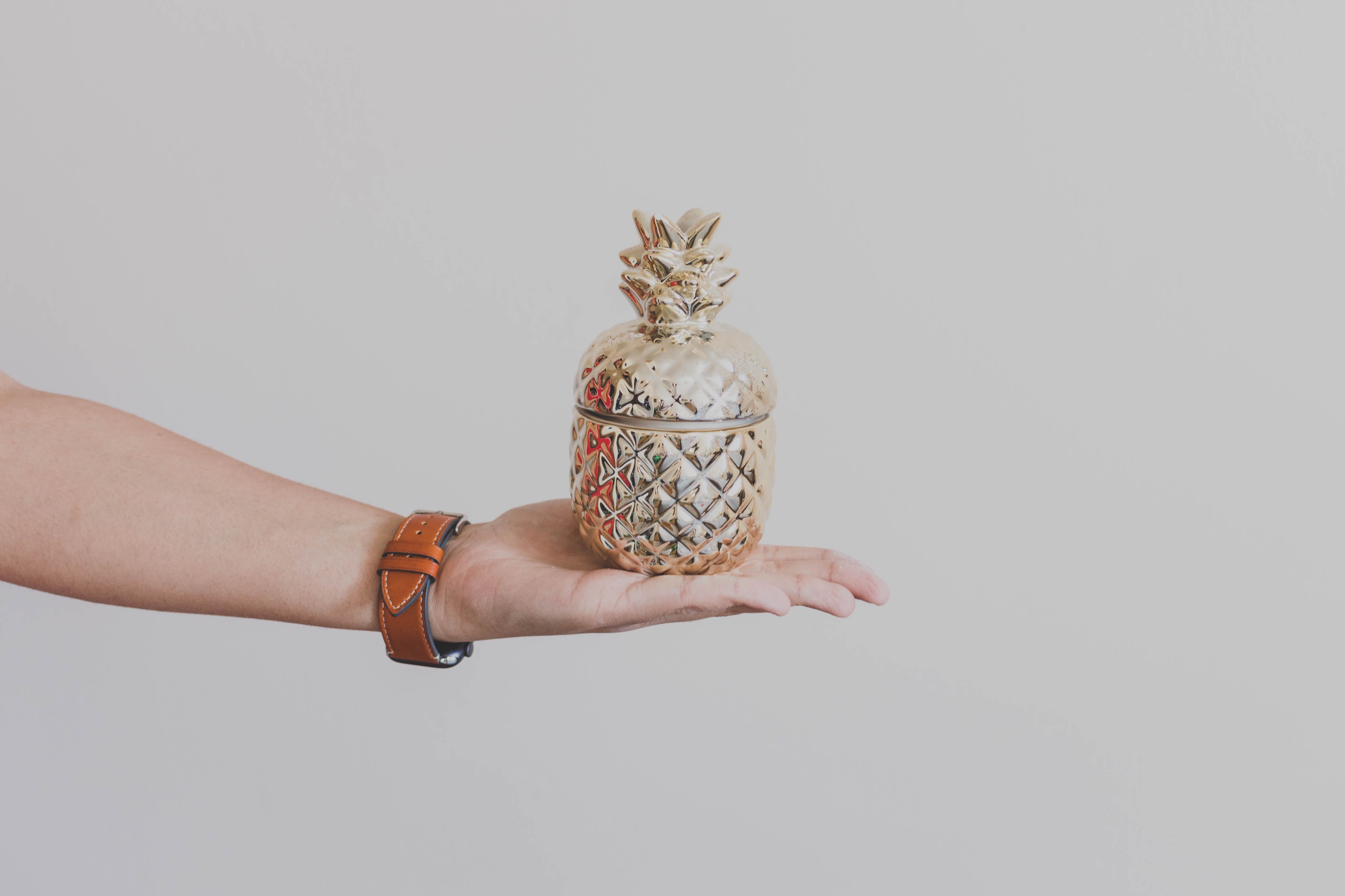 person holding gold-colored pineapple design rack