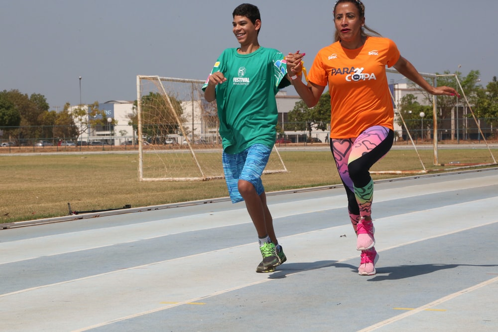 two man and boy running on track field during daytime