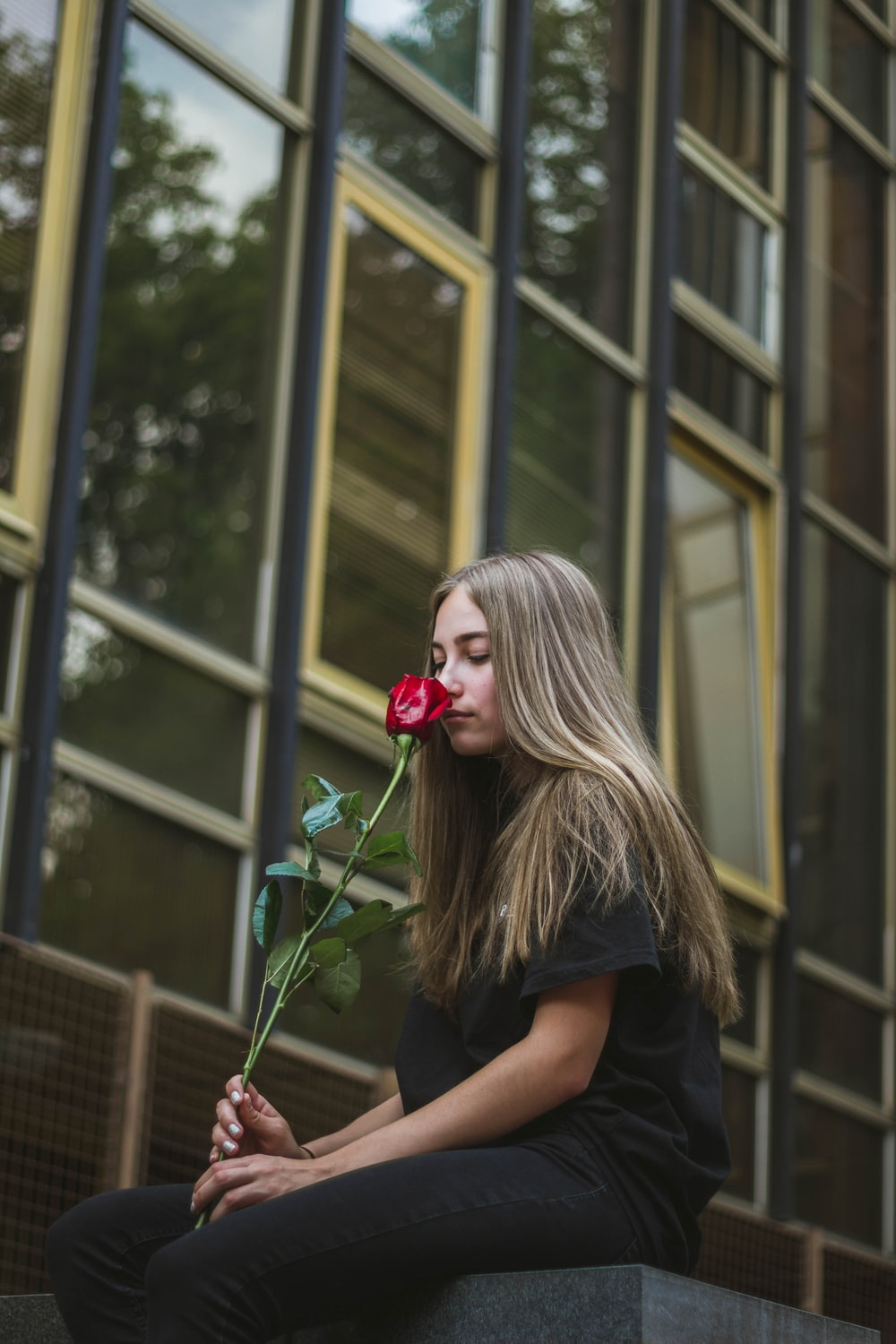 woman smells red rose