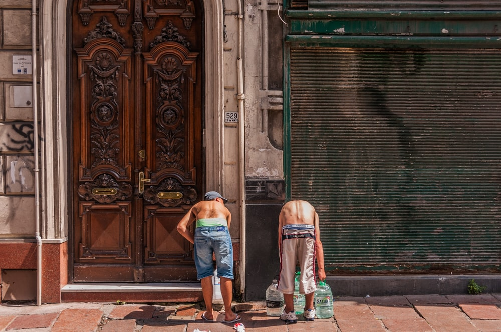 two men wearing brown shorts near closed brown doors outside building