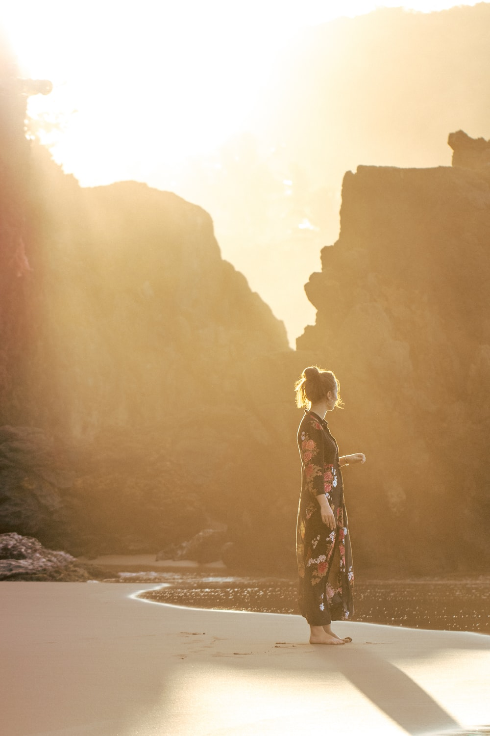 woman standing on shore during golden hour