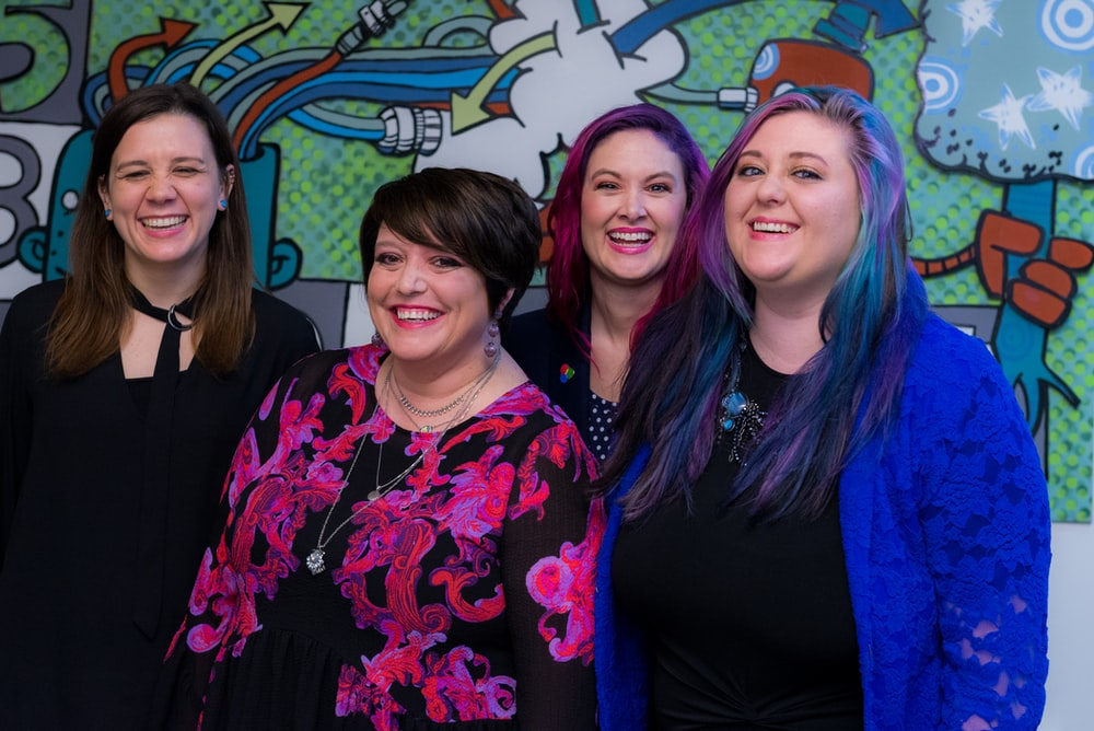 four smiling womens standing inside room