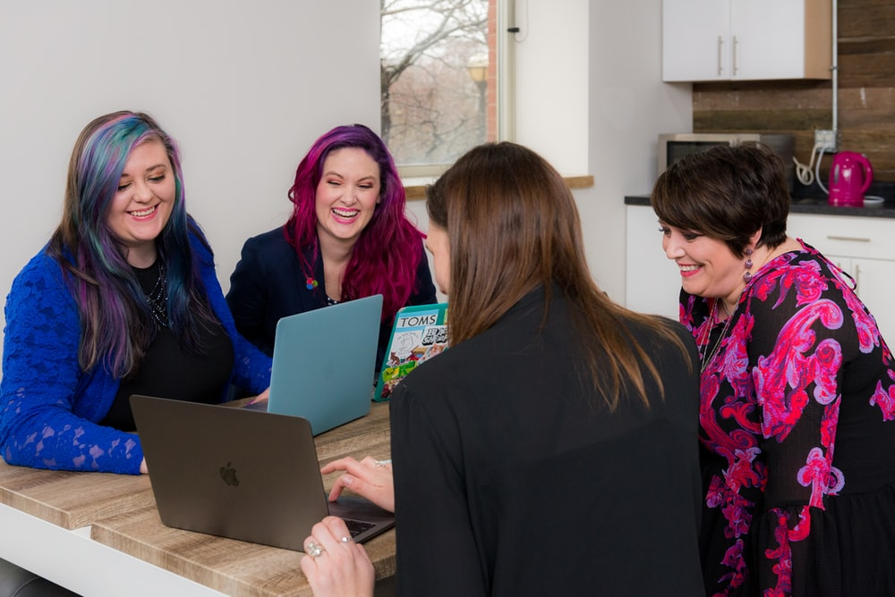 four woman on brown wooden table looking at laptops