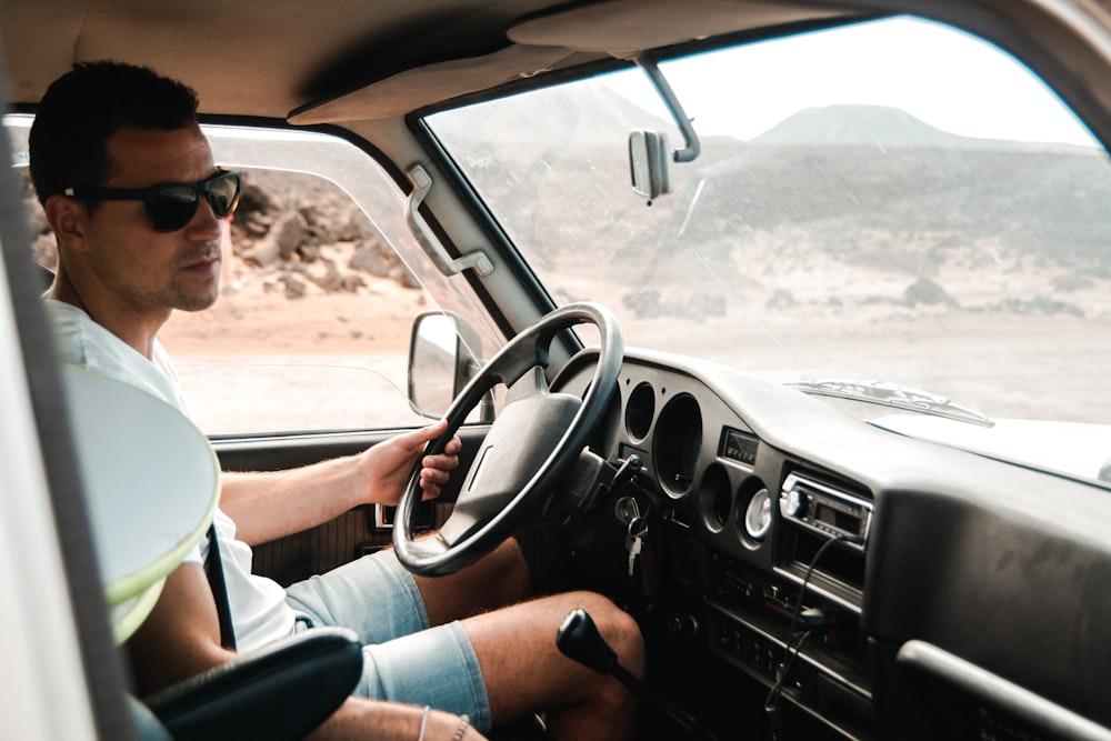 man wearing white crew-neck shirt holding steering wheel