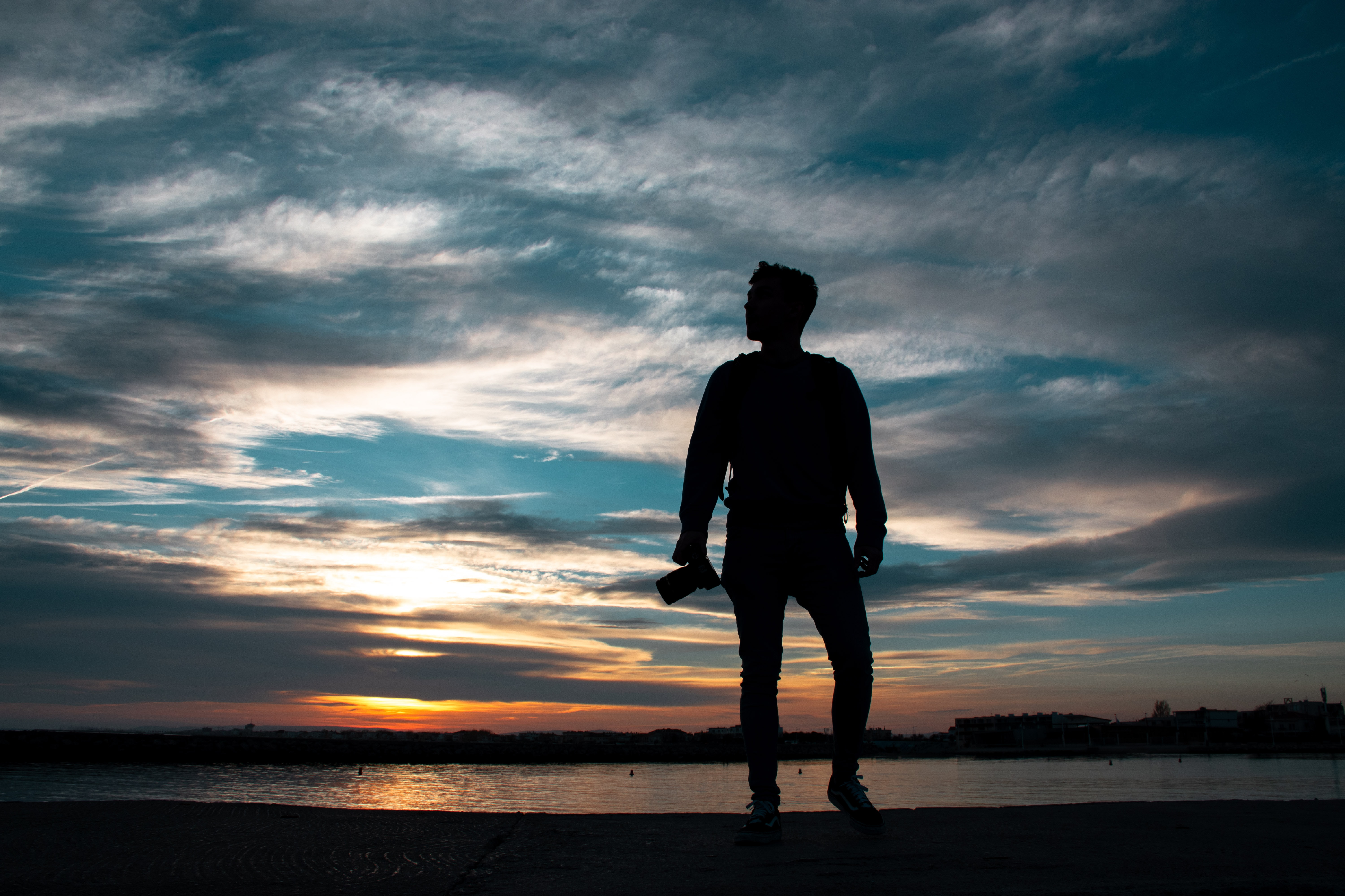 silhouette of man standing holding camera