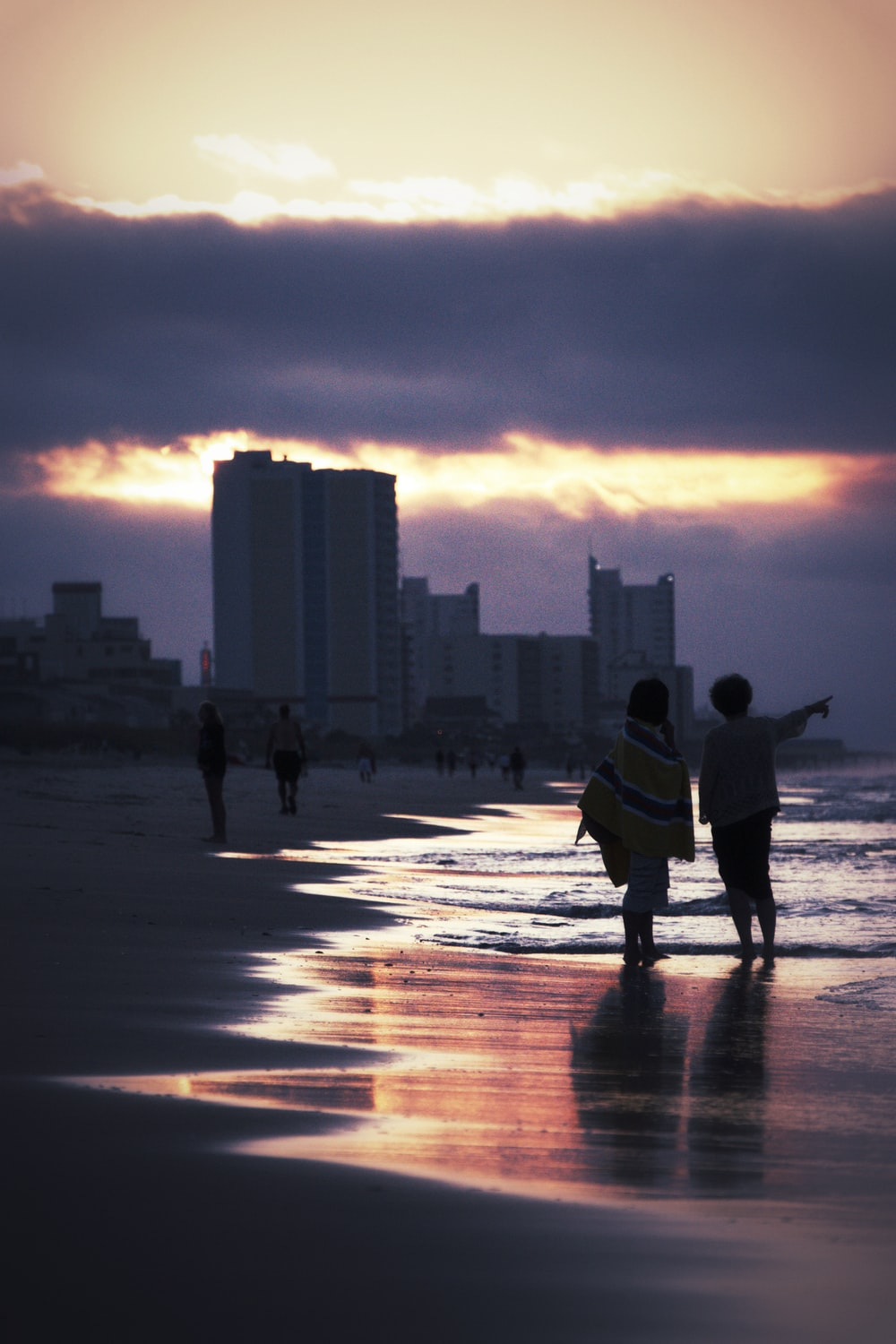 two people walking on seashore near buildings during golden hour