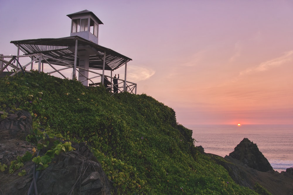 white lighthouse across sunset
