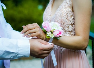 man putting pink and white floral decor to woman's hand