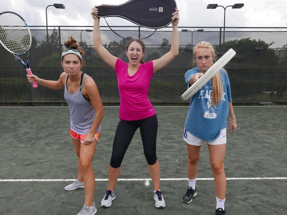 three women holding tennis rackets